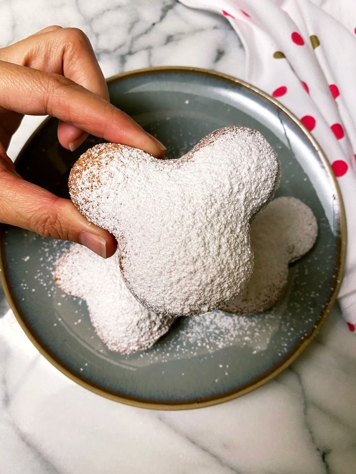 a hand holding a Mickey beignet on a plate topped with powdered sugar