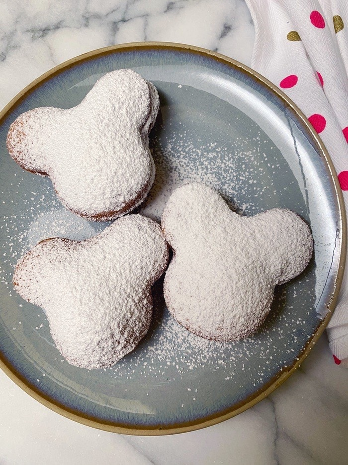 Mickey shaped beignets on a plate topped with powdered sugar