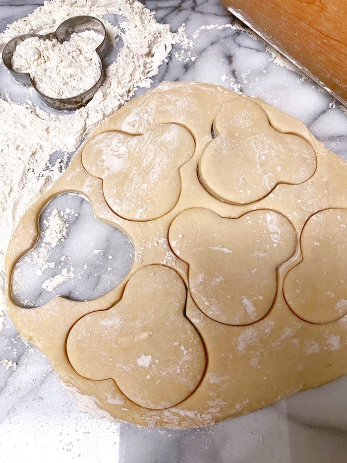 Mickey Mouse shaped cut out dough with flour and cookie cutter in the background